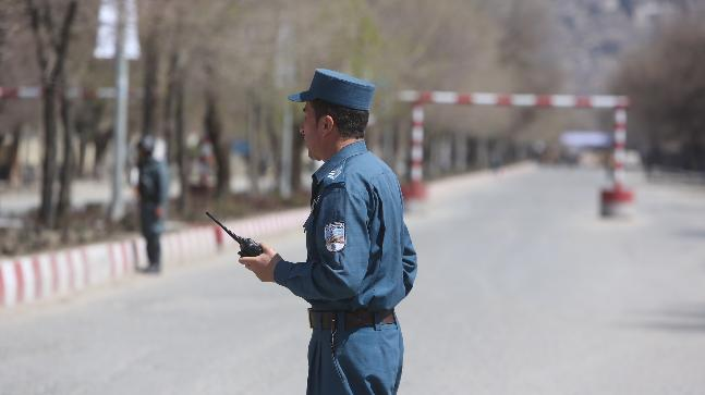 Police stand guard in the street after a suicide attack in front of the Kabul university in Kabul