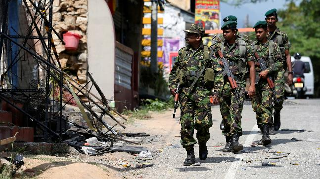 Sri Lanka's Special Task Force soldiers walk past a damaged houses after a clash between two communities in Digana central district of Kandy. (Reuters image)
