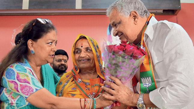 Reluctant handshake: Kirori Lal Meena and his wife with Vasundhara Raje in Jaipur