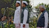 Rahul Gandhi (C), president of India's main opposition Congress party, stands to attention after hoisting the party's flag on its 133rd Foundation Day