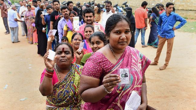 People queue up to cast their ballot in Bengaluru on Saturday. (Photo: PTI)
