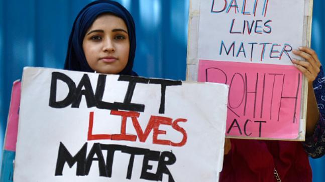 Protestors holding up signs against caste violence