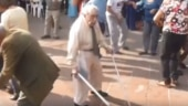 An old man in a market square in Mexico dances with a lot of energy.