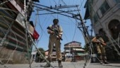 Policemen stand guard behind concertina wire during a strike called by separatists in Srinagar. (Photo: Reuters)