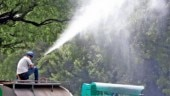 NDMC workers sprinkle water on trees to wash away settled dust. (Photo: Kasif)