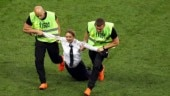 Stewards drag a woman who invaded the pitch during the final match between France and Croatia (AP Photo)