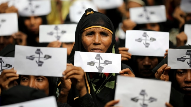 Rohingya refugee women hold placards as they take part in a protest at the Kutupalong refugee camp to mark the one-year anniversary of their exodus