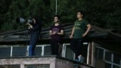 Female photographer covers men's football match in Iran from a rooftop