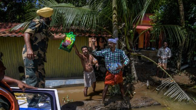 Border Security Force (BSF) distribute food food and water to the residents who are stuck in their houses as well who have not vacated houses because of the flood water in interior places at Allapy in Kerala, India. (Photo courtesy: Getty Images)