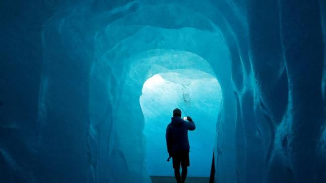 A tourist takes a picture in the Ice Cave at the Rhone Glacier in Furka, Switzerland, September 13, 2018. (Reuters)