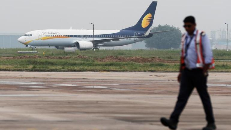 A Jet Airways Boeing 737-800 passenger plane moves on the runway as a man walks past at an airport in New Delhi. (Photo: Reuters)