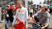 All in good fun: Vettel throws Mercedes cap on the ground, offers young fan Ferrari hat