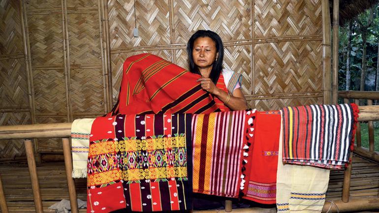 FINE PRINT: A tribal woman shows handloom products made for tourists. (Photo: Manash Jyoti Dutta)