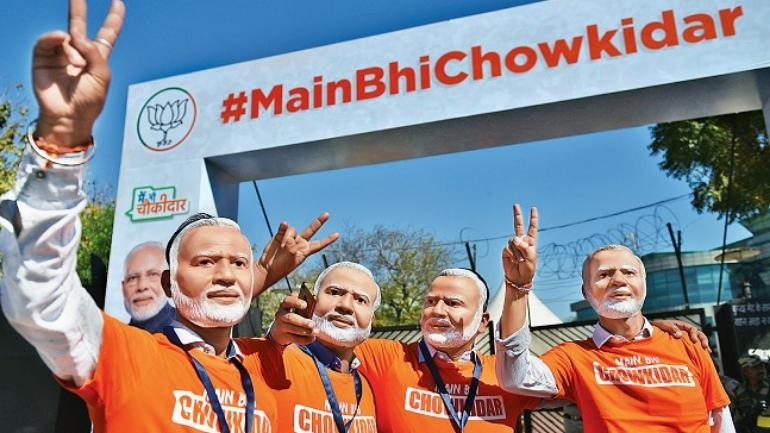 "BJP supporters wear masks of PM Narendra Modi during his speech as part of the ""Main bhi Chowkidar"" campaign, at Talkatora Stadium in New Delhi on Sunday. (Photo: Kasif)"
