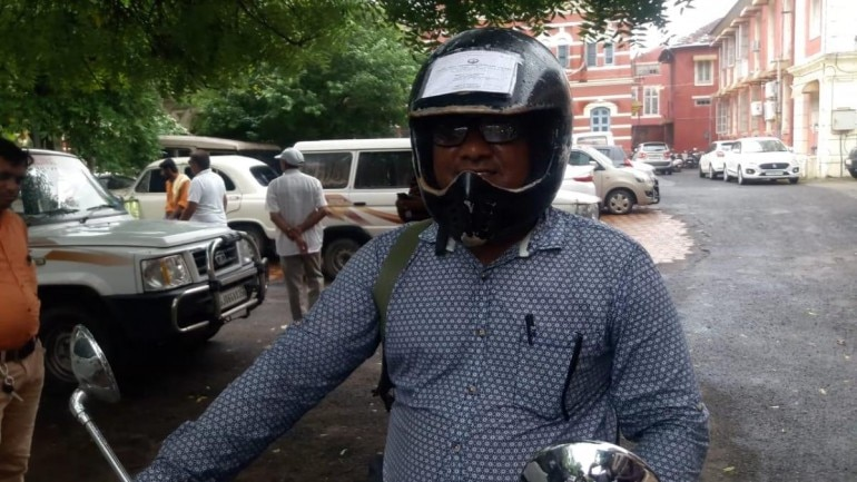 Man wears helmet with license and other documents pasted on it
