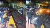 Woman almost gets run over by train after man faints and knocks her on tracks. Chilling video