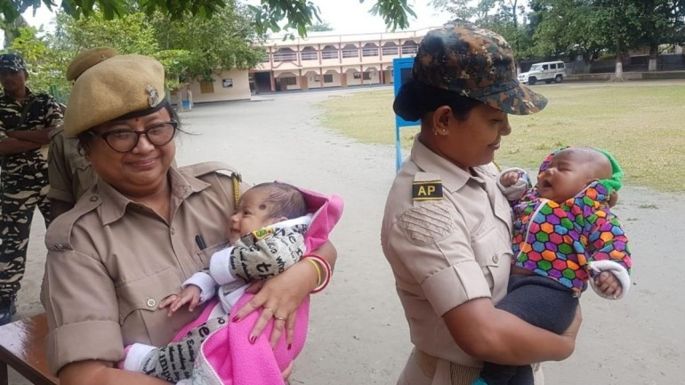 Two police women from Assam holding babies as their mother took TET exams inside. (Photo: Twitter)