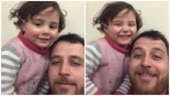 Syrian dad tells daughter sound of bombs is from toy guns, asks her to laugh. Heartbreaking video