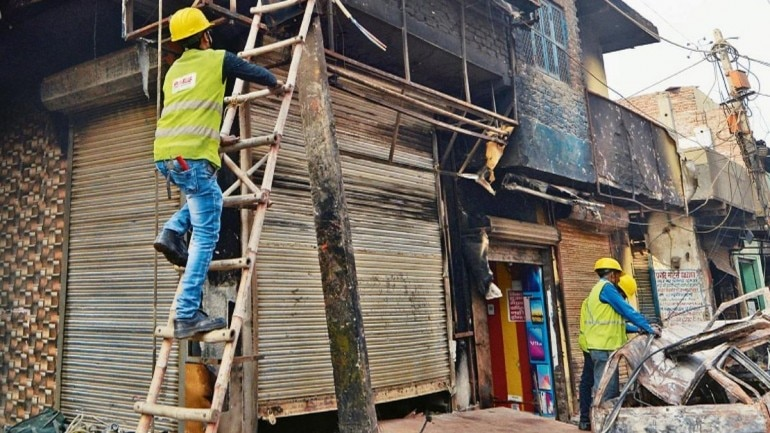 Electricity dept workers repair supply lines damaged in northeast Delhi clashes, on Friday. (Photo: Pankaj Nangia)