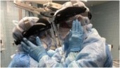 Healthcare worker-couple in hazmat suits and masks share emotional moment in hospital. Viral pic