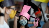 Artists wear colourful hats made of paper mache Photo: Reuters