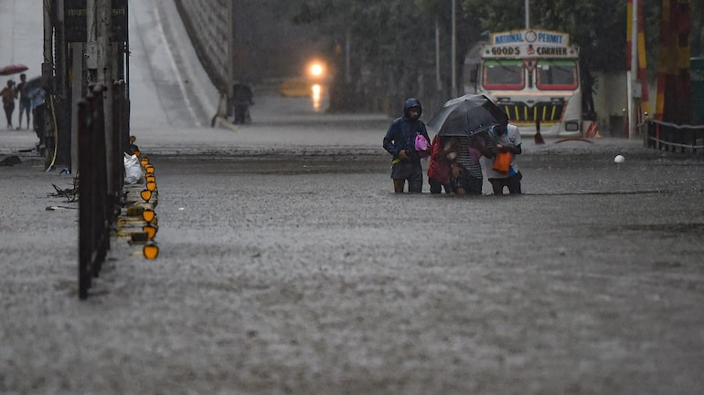 People crossing a water-logged street in Mumbai's Sion on Wednesday