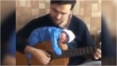 Father plays guitar with his newborn baby. Adorable viral video