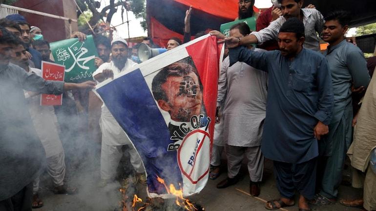 [REPRESENTATIVE IMAGE]  حامیان یک حزب سیاسی مذهبی نمایشی از پرچم فرانسه را که چهره رئیس جمهور امانوئل مکرون در آن بود ، در کراچی در 13 نوامبر سوزاندند