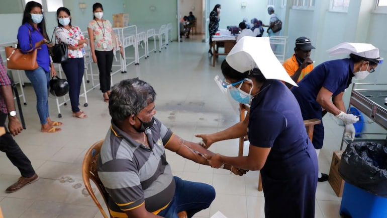 A Sri Lankan nurse takes a blood sample from a municipal worker before administering Covid-19 vaccine in Colombo on February 15, 2021