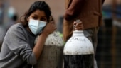 Top photo: A woman rests her head on oxygen cylinders after having managed to get them refilled at a factory in Kathmandu