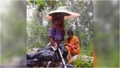 Man holds umbrella to protect daughter from rain as she attends online class by the road. Viral pic
