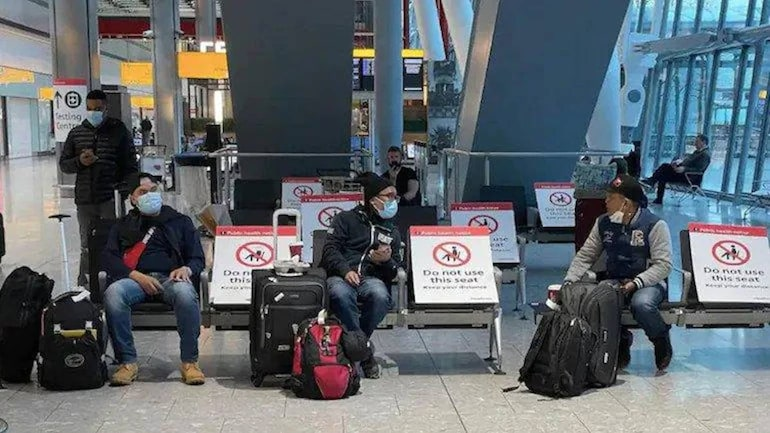 Passengers sitting in waiting area of London's Heathrow Airport
