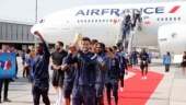 France's victorious World Cup team returned home from Russia to triumphant arcs of water heralding their airplane's arrival and a red carpet welcome on Monday.