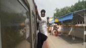 student hanging from train