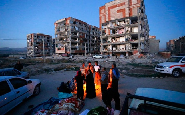 Survivors of the earthquake warm themselves in front of destroyed buildings at the city of Sarpol-e-Zahab in western Iran. Photo: Pouria Pakizeh/ISNA via AP