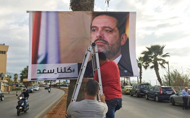 Workers hang a poster of Prime Minister Saad Hariri in the Lebanese capital Beirut. Hariri's shocking announcement of his resignation - made from Saudi Arabia - has fueled speculation that he may be held against his will. (Photo: AP)