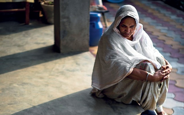 Manu's mother Sukhwinder stares at his blood-soaked clothes and shoes.