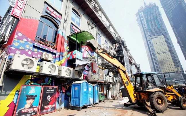 BMC bulldozer takes down illegally constructed eateries in the Kamala Mills compound following the fire incident, in Mumbai. (Photo: PTI)