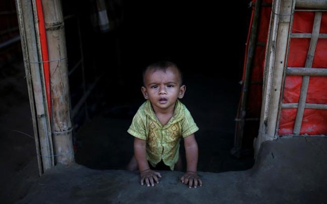 A Rohingya refugee baby sits at the entrance of his family's temporary shelter at a refugee camp near Cox's Bazar, Bangladesh (Photo: Reuters)