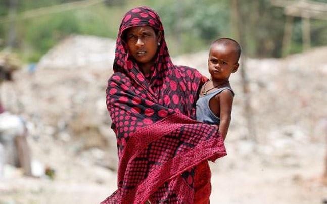A Rohingya woman walks through a camp in Delhi