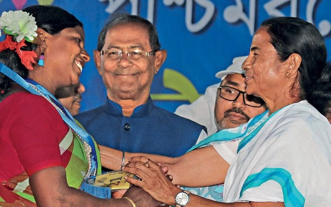 CM Mamata Banerjee interacting with a beneficiary at Ahmadpur in Birbhum district. Source: PTI