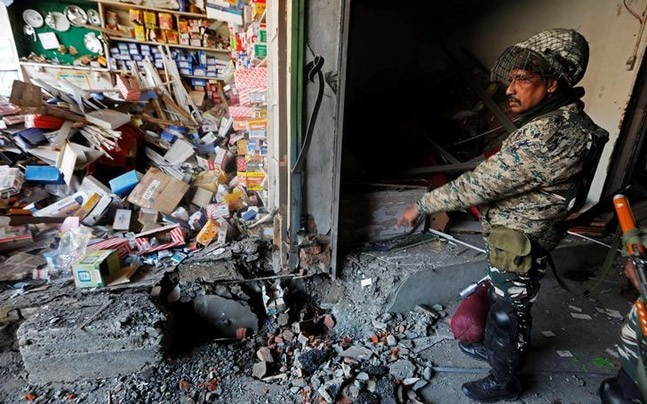 An Indian policeman inspects the site of an explosion where according to local media four policemen died when suspected militants set off an improvised explosive device (IED) at a market in Sopore, north Kashmir, January 6, 2018. (Photo: Reuters)