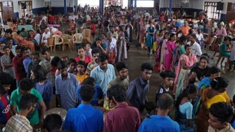 Flood victims wait for food inside a college auditorium, which has been converted into a temporary relief camp, in Kochi.