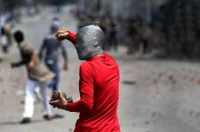 A stone-throwing youth in Kashmir.