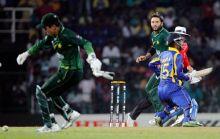 Pakistan captain Shahid Afridi (rear) watches as Sri Lanka batsman Chamara Silva stops his run and wicketkeeper Kamran Akmal approaches to collect the ball
