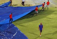 Ground staff work as Rajasthan captain Shane Warne walks back after inspecting the pitch