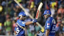 Mumbai batsman Rohit Sharma raises his bat to mark his half-century against Hyderabad as Andrew Symonds looks on