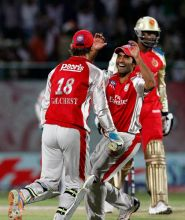 Punjab's Dinesh Karthik (centre) and captain Adam Gilchrist celebrate the dismissal of Bangalore opener Chris Gayle