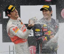 McLaren Mercedes driver Jenson Button and Red Bull driver Mark Webber spray champagne