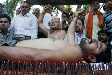 An Rashtriya Swabhiman Andolan worker lies down on a bed of nails